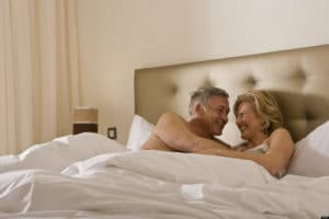 Casal maduro se abraçando na cama